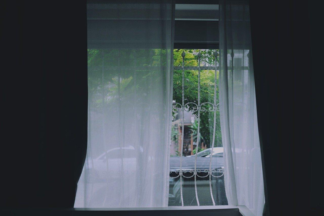 白いカーテンが窓にかかっている