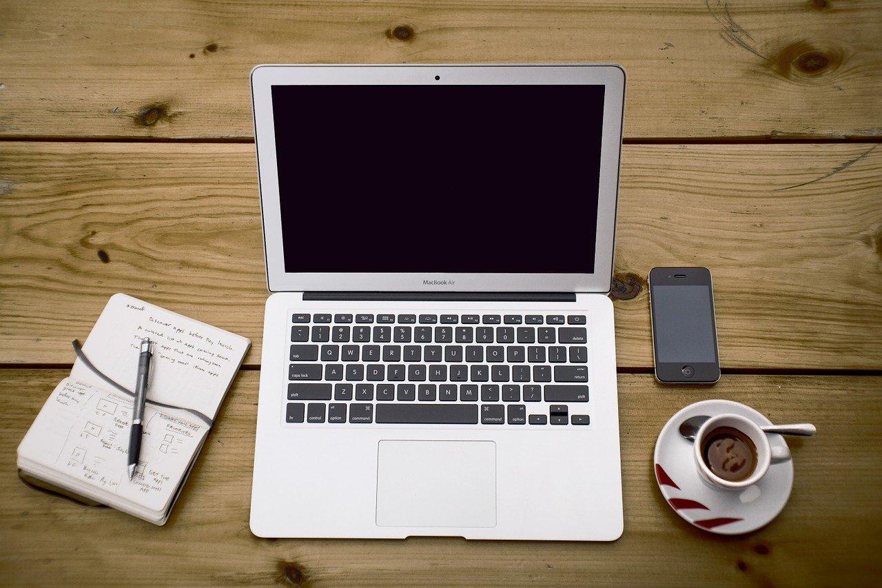 テーブルの上にパソコン、スマホ、コーヒーが置かれている