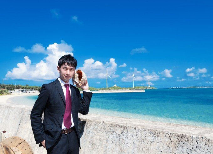 海辺で男が貝に耳を澄ましている